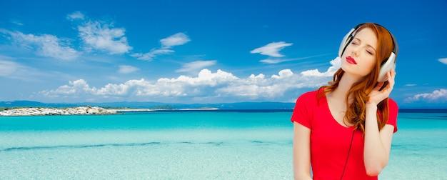 Молодая рыжая девушка в красном платье слушает музыку через наушники на летнем морском пляже
