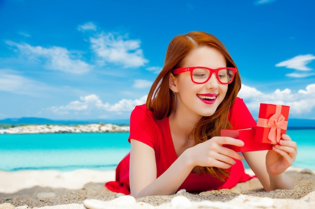 Молодая рыжая девушка в красном платье с подарочной коробкой отдыхает на летнем морском пляже