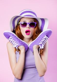 Молодая рыжая девушка в солнцезащитных очках и шляпе, держащая туфли на розовом