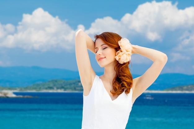 Молодая рыжая девушка в белом платье с цветком в волосах отдыхает на летнем морском пляже