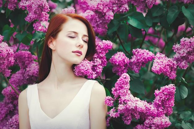公園のライラックの茂みの近くに立っている白いドレスの若い赤毛の女の子。