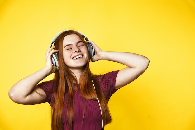 Young redhead girl is happy and listening music via headphones with closed eyes