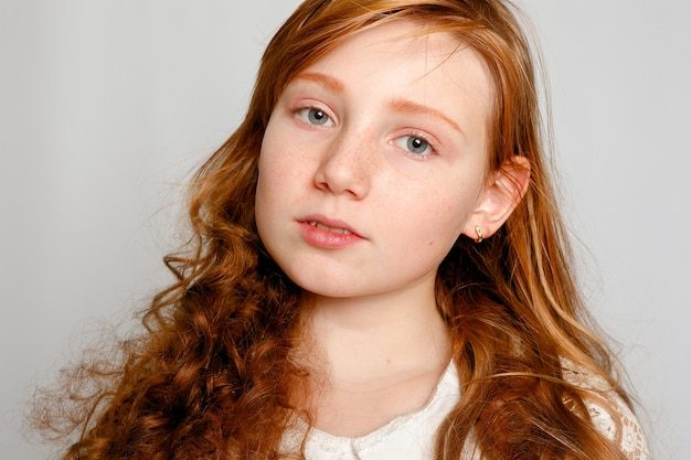Young redhead girl posing on grey background