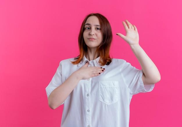 胸に手を置き、ピンクの壁に分離された停止ジェスチャーを示す若い赤毛の女の子