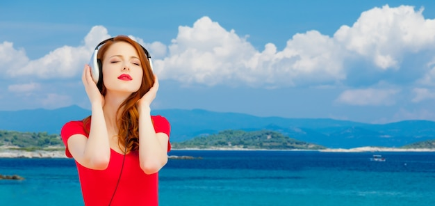 Young redhead girl in red dress listening music via headphones on summertime sea beach