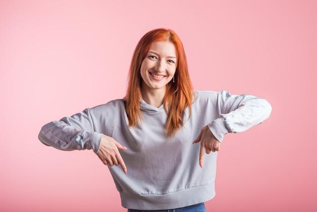 ピンクの背景にスタジオで人差し指を示す若い赤毛の女の子