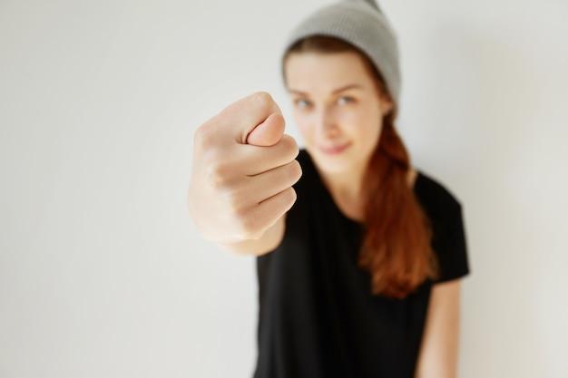 Молодая рыжая девушка в шляпе и черной футболке