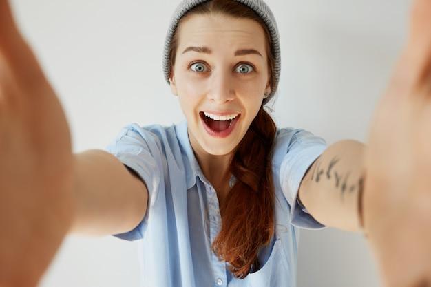 Молодая рыжая девушка в шляпе и синей рубашке