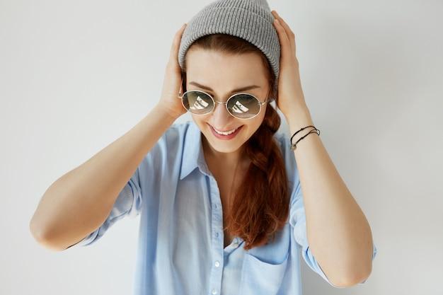 Молодая рыжая девушка в солнцезащитных очках и шляпе