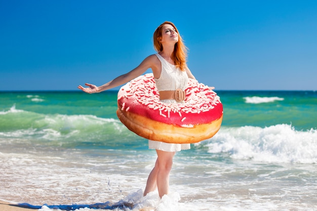 Young redhead girl with donut at the waist