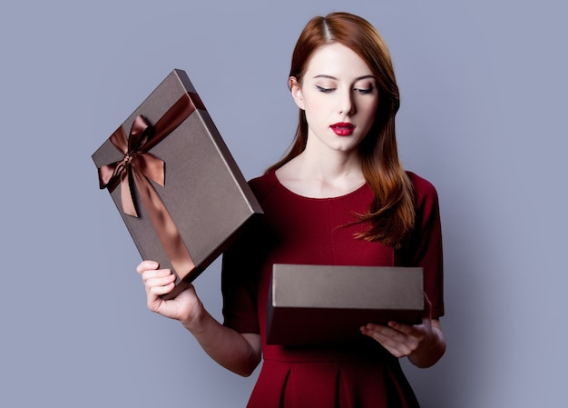 Young redhead girl with gift box on grey