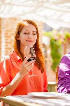 Молодая рыжая девушка с бокалом вина в ресторане в летнее время.