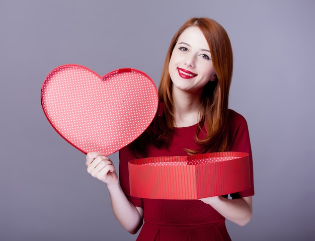 Young redhead girl with hearth shape box on grey.
