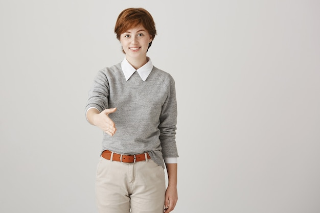 Young redhead girl with short haircut posing against the white wall