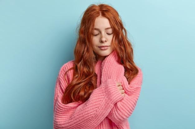 Молодая рыжая девушка с волнистыми волосами