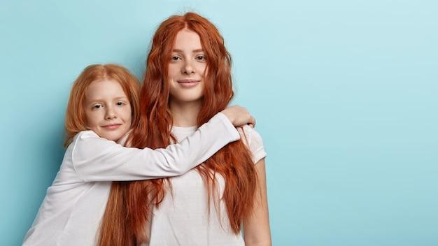 Giovani ragazze della testarossa che propongono insieme