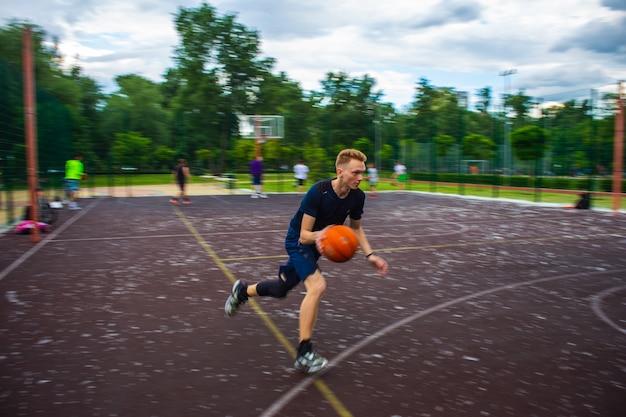 낮 동안 운동이 흐려지는 동안 거리에 있는 운동장에서 빠른 속도로 농구공을 달리고 드리블하는 젊은 빨간 머리 남자