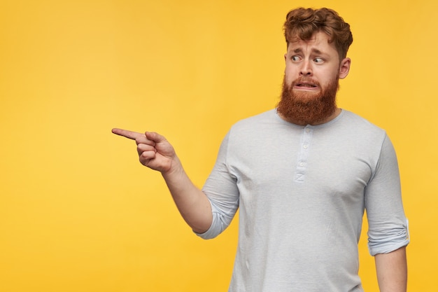 Giovane ragazzo dai capelli rossi con una grande barba rossa, si sente irritato e confuso, indica con un dito in uno spazio di copia