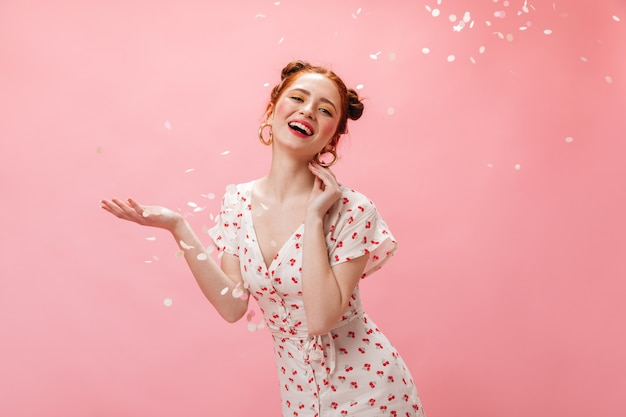Young redhead lady in white dress smiles coquettishly. woman with yellow eye shadows posing on pink background with confetti.