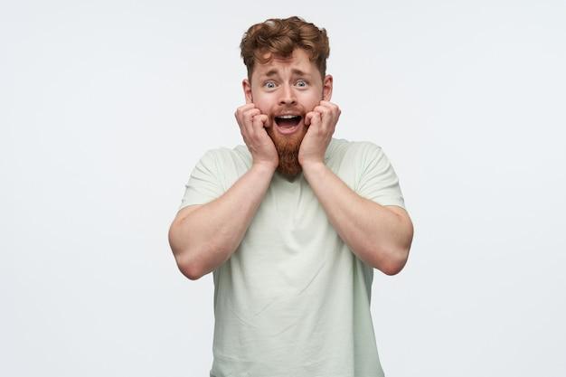 Giovane maschio rosso con una grande barba con un'espressione facciale spaventata