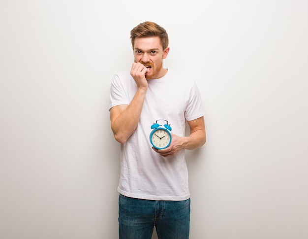 Young redhead man biting nails, nervous and very anxious. he is holding an alarm clock.