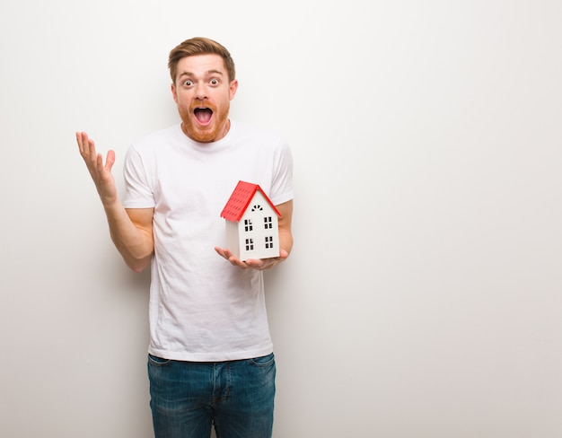 Young redhead man celebrating a victory or success. holding a house model.