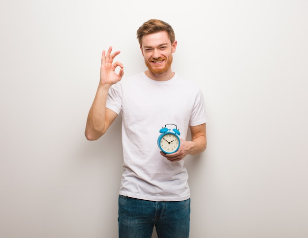 Young redhead man cheerful and confident doing ok gesture. he is holding an alarm clock.