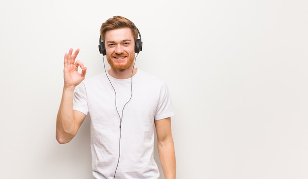 Young redhead man cheerful and confident doing ok gesture and listening to music with headphones