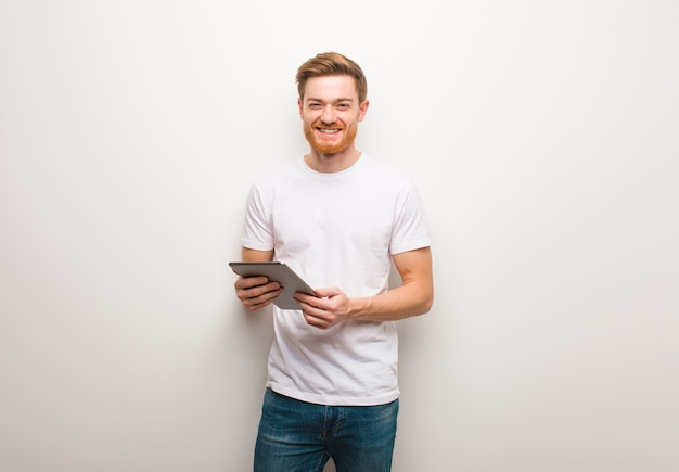 Young redhead man cheerful with a big smile. holding a tablet.
