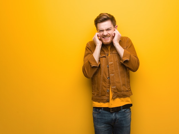 Young redhead man covering ears with hands