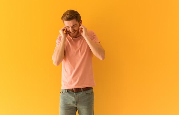 Рыжий молодой человек, охватывающий уши руками