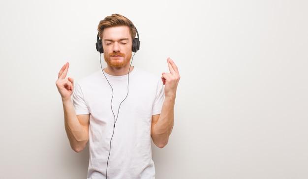 若い赤毛の男が運を持っているための指を交差します。ヘッドフォンで音楽を聴く。