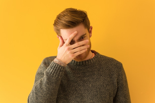 Young redhead man face closeup embarrassed and laughing at the same time