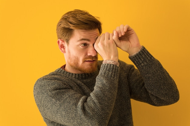 Young redhead man face closeup making the gesture of a spyglass
