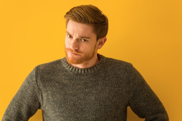Young redhead man face closeup scolding someone very angry