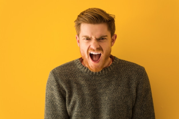 Young redhead man face closeup screaming very angry and aggressive