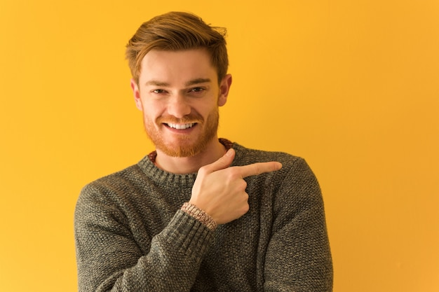 Young redhead man face closeup smiling and pointing to the side