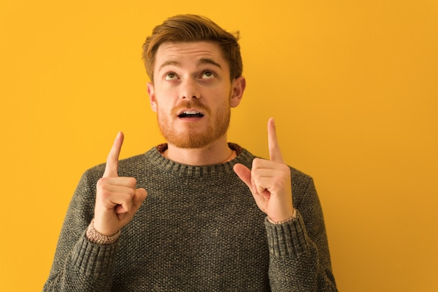 Young redhead man face closeup surprised pointing up to show something