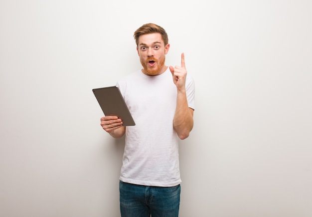Young redhead man having a great idea, concept of creativity. holding a tablet.