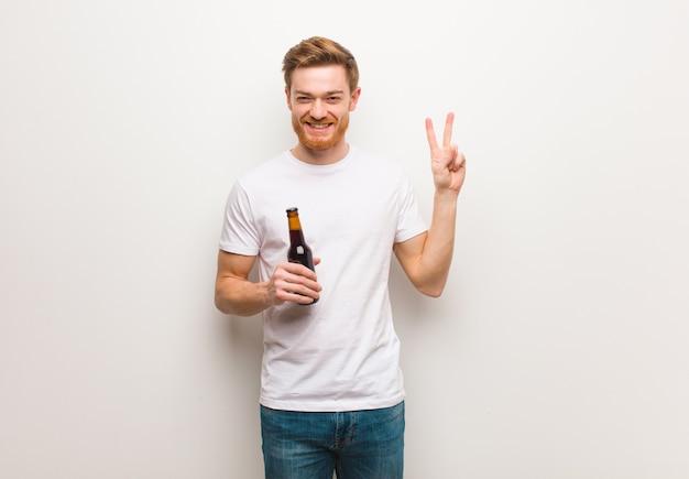 젊은 빨강 머리 남자. 맥주를 들고.