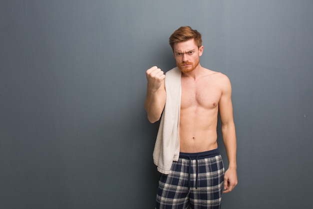 Молодой рыжий мужчина держит полотенце, показывая кулаком вперед, сердитое выражение. он держит белое полотенце.
