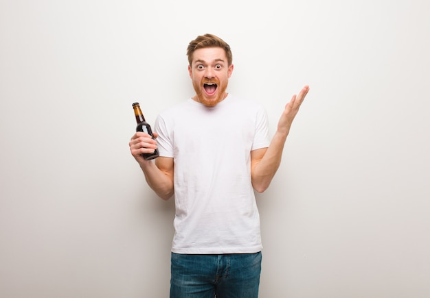 Young redhead man. holding a beer.