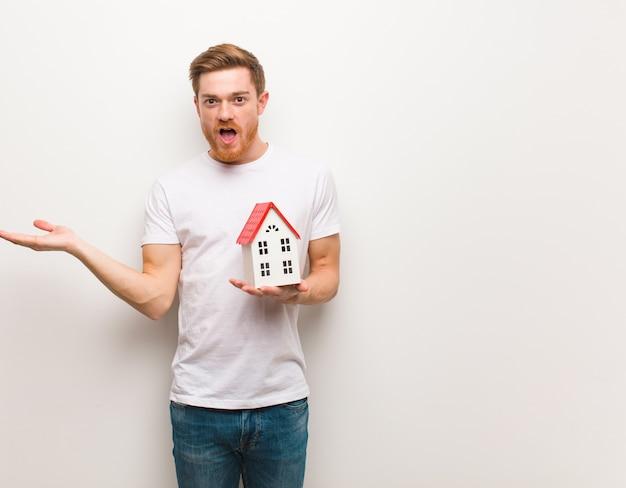 手のひらの手に何かを持っている若い赤毛の男。家のモデルを保持しています。