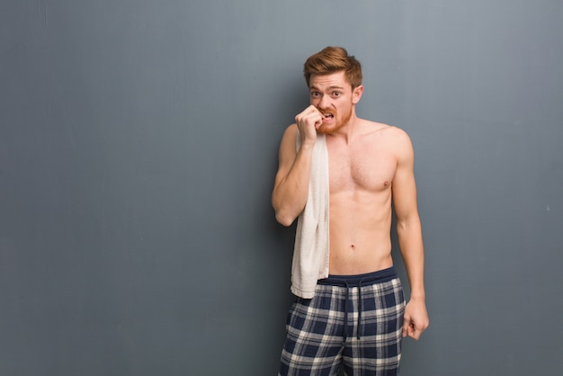 Young redhead man holding a towel biting nails, nervous and very anxious. he is holding a white towel.