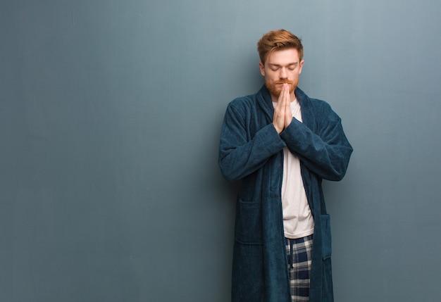 非常に幸せで自信を持って祈るパジャマの若い赤毛の男