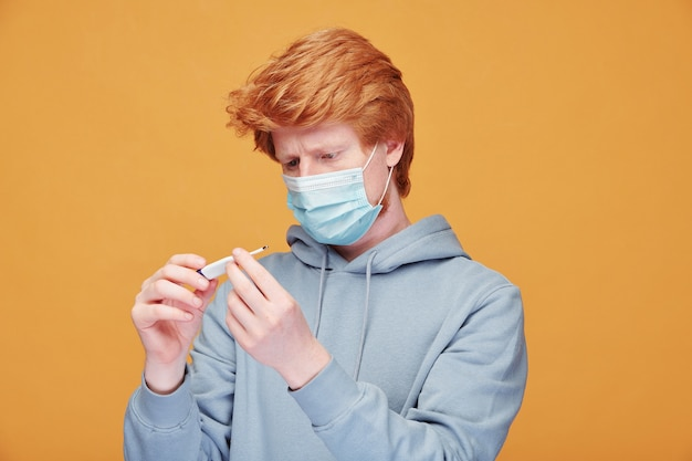 Young redhead man in mask standing on orange and checking body temperature on electronic thermometer