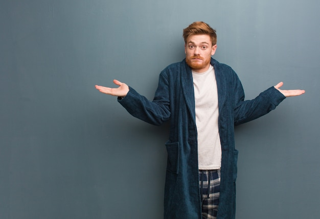 Young redhead man in pajama confused and doubtful