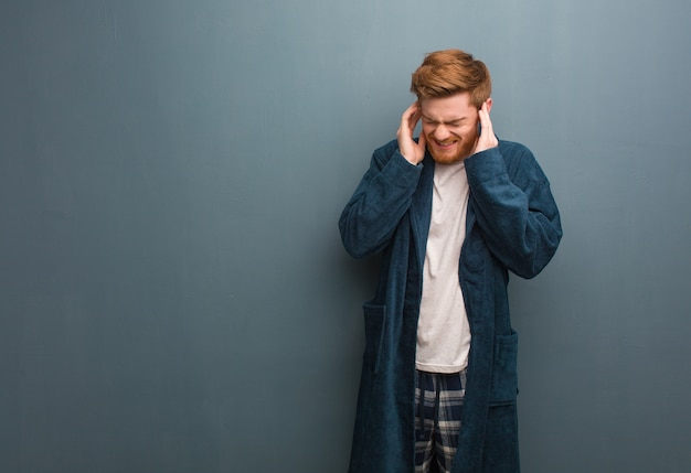 Young redhead man in pajama covering ears with hands