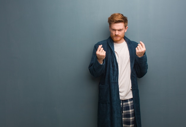 Young redhead man in pajama doing a gesture of need