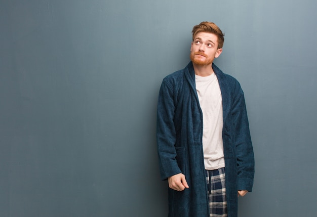 Young redhead man in pajama dreaming of achieving goals and purposes